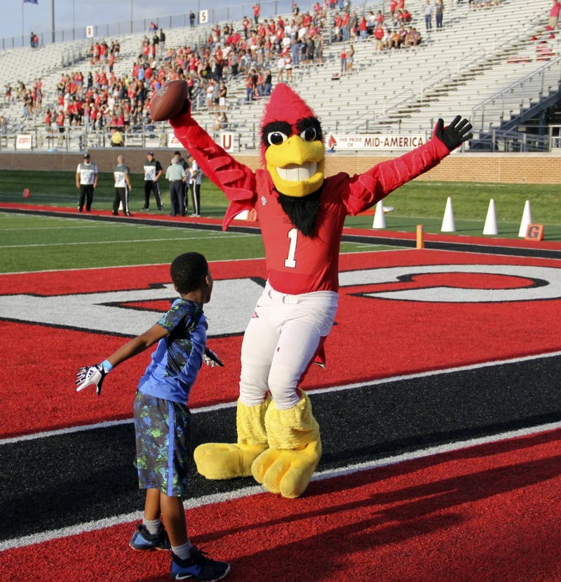 Charlie Cardinal plays football with a young Ball State fan before the Cardinals' game against Central Connecticut State Thursday, Aug. 31, 2018 at Scheumann Stadium. Charlie Cardinal is Ball State's Mascot. Paige Grider, DN
