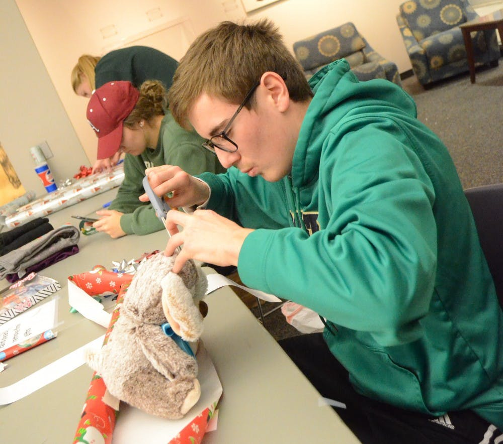 Elementary education major Nicholas Toby wraps a teddy bear during Angel's Tree gift wrapping event Dec. 3, 2018. Toby was one of 85 volunteers who helped wrap gifts. Alyssa Cooper,DN.