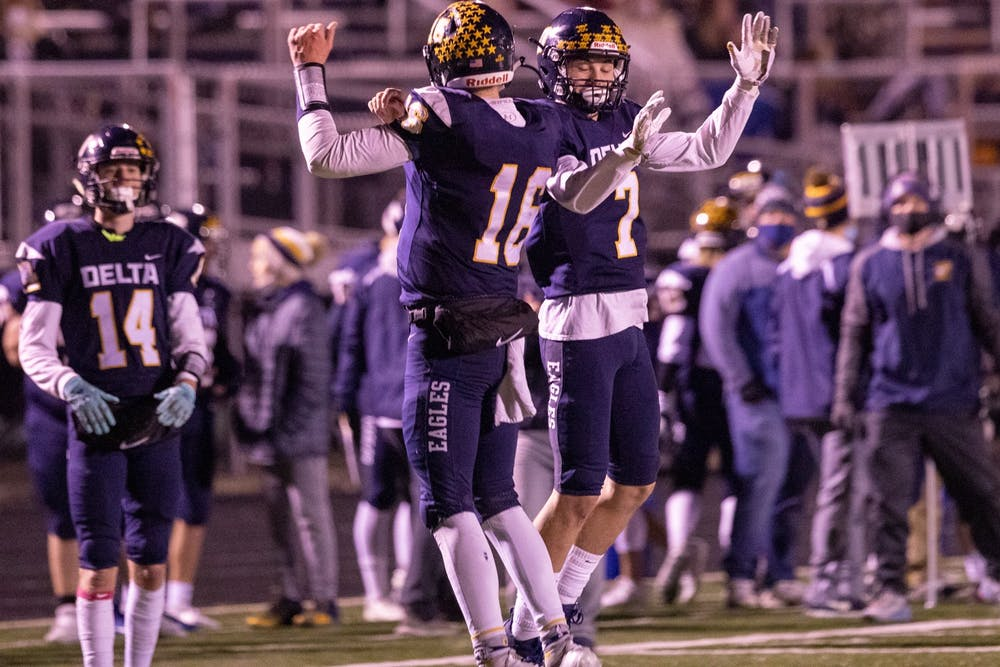 <p>Delta senior quarterback Brady Hunt celebrated with Delta junior running back Parker Faletic in the third quarter against Wayne High School Oct. 30, 2020, at Delta High School. The Eagles beat the Generals 49-18. Jacob Musselman, DN</p>