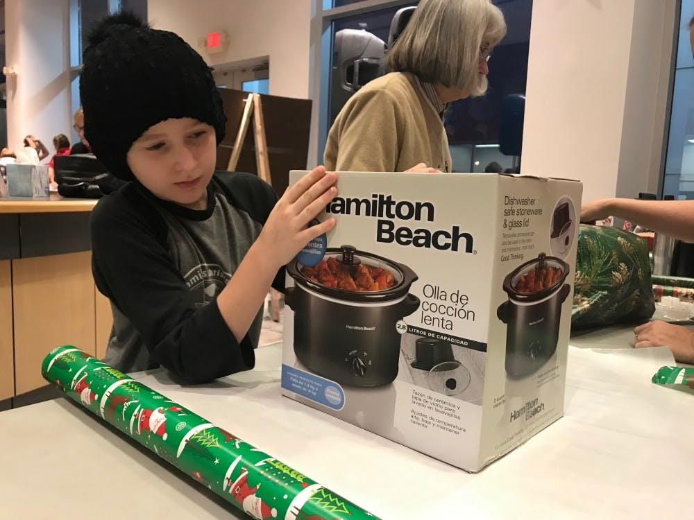 Nine-year-old Ellie Anderson participates in her third year at Secret Families. Anderson was part of the first shift of wrappers, which began wrapping gifts at 7:30 a.m. Anderson said she was excited to help give presents to those who don't have as much as her.Hannah Gunnell, DN
