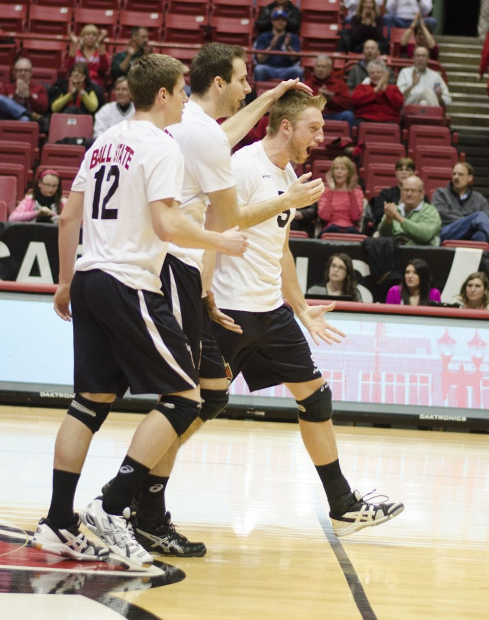 Senior outside attacker Matt Sutherland, senior middle attacker Matt Leske and senior setting Graham McIlvaine celebrate after getting a point in the first set against Mount Olive on March 1 at Worthen Arena. DN PHOTO BREANNA DAUGHERTY