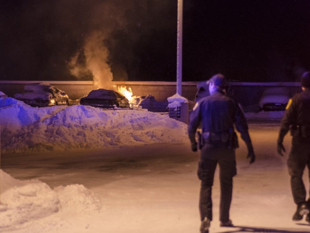 Kyle Kincer's car continues to burn as University Police Department officers clear the area around the top floor of the McKinley Avenue parking garage. The fire began after Kincer locked the keys inside the car and left it running while trying to find help. DN PHOTO COREY OHLENKAMP