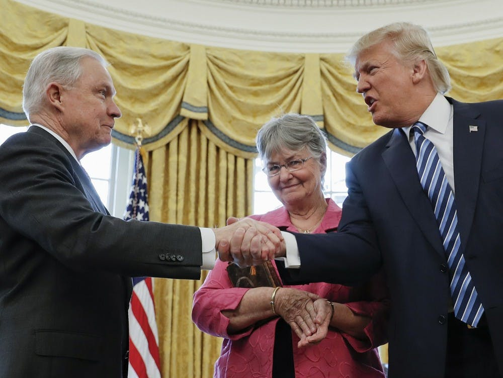 In this Feb. 9, 2017 file photo, President Donald Trump shakes hands with Attorney General Jeff Sessions, accompanied by his wife Mary, after he was sworn-in by Vice President Mike Pence, in the Oval Office of the White House in Washington. On Nov. 7, 2018, Sessions submitted his resignation in letter to Trump. (AP Photo/Pablo Martinez Monsivais, File)