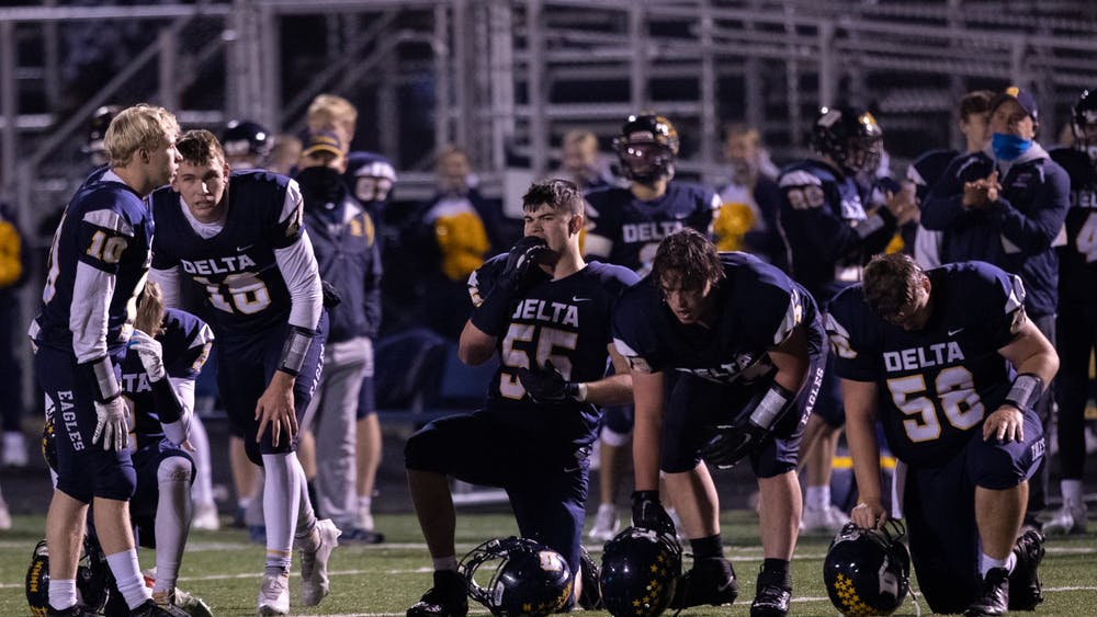 The Delta Eagles kneel down for their hurt teammate during an injury timeout Oct. 30, 2020, at Delta High School. The Eagles beat the Generals 48-18. Jacob Musselman, DN