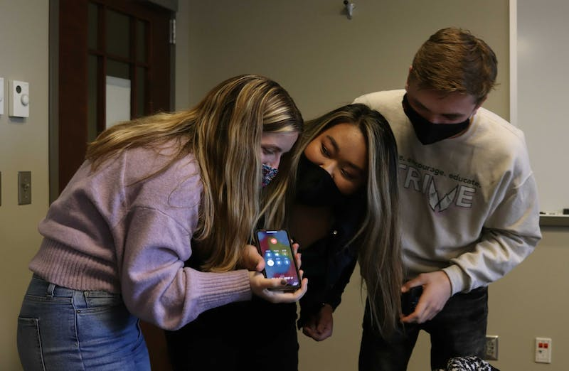 Chiara Biddle, Strive slate vice president elect, Tina Nguyen, president elect, and Joseph Gassensmith, Strive campaign manager, listen to a phone call from Parker Abrell, SGA elections commissioner, March 2, 2021 in a Kinghorn Hall conference room. Abrell called the slate about five minutes after voting closed to congratulate slate members on their win. Rylan Capper, DN