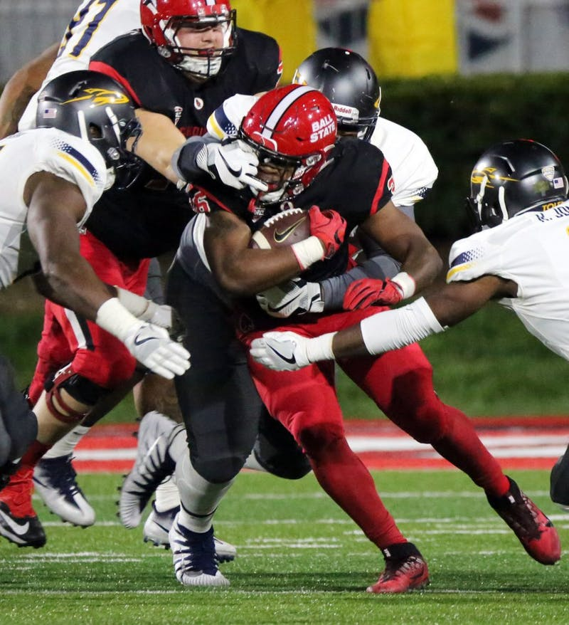 Freshman running back Caleb Huntley runs the ball while a Toleo defensive player grabs his face mask during the Cardinals' game against the Rockets on Oct. 26 at Scheumann Stadium. Huntley had 95 rushing yards for gain. Paige Grider, DN File