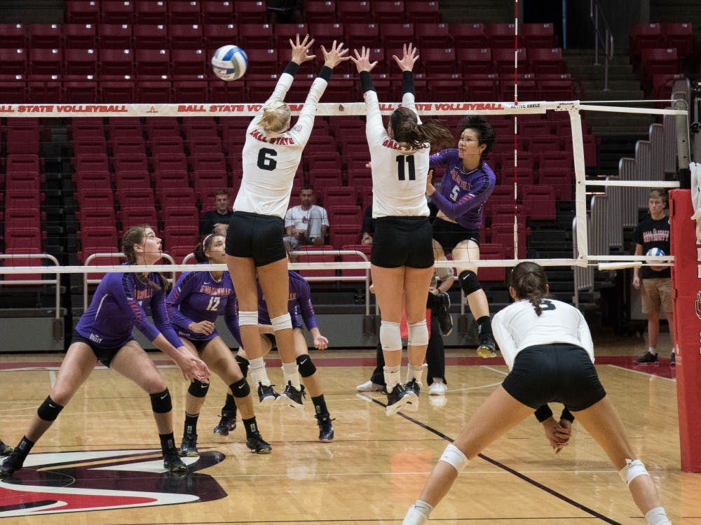 (Left) Redshirt junior middle hitter Avery Devoe and Sophomore setter Amber Seaman block the ball at the game against Evansville on Sept.14 at John E. Worthen Arena. The Cardinals had six blocks throughout the game. Emily Coats, DN File