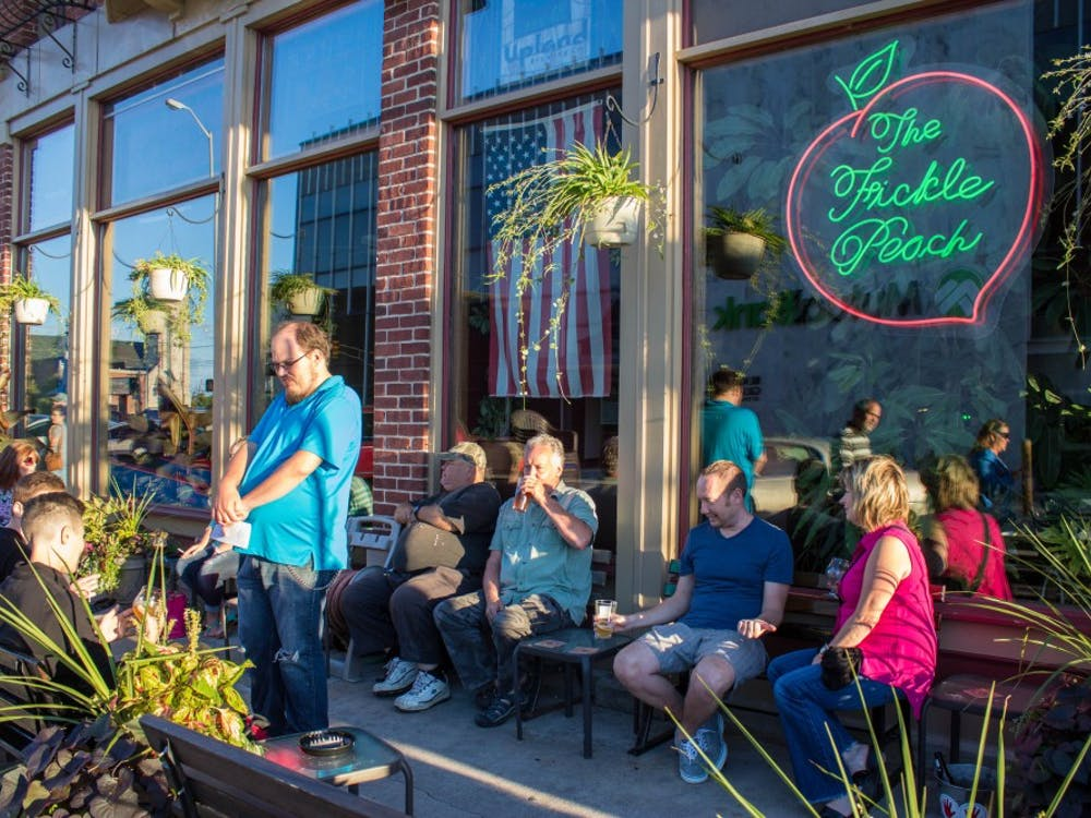Customers sit on the patio of The Fickle Peach listening to live music by the Tuesday Nite String Band on Sept. 1. The bar and restaurant was one stop in the community event First Thursday, which showcased Muncie's local artists. Grace Ramey // DN
