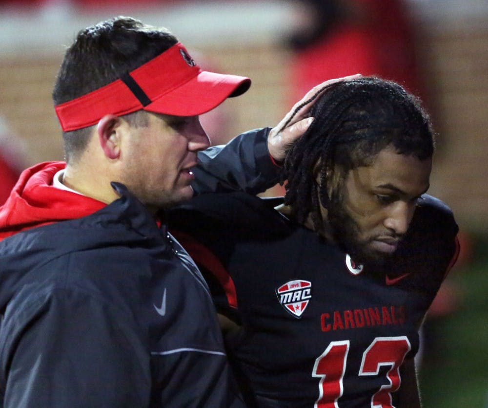 Redshirt senior cornerback David Moore gets a hug from a coach after the Cardinals' game against Miami Ohio on Nov. 21 at Scheumann Stadium. Ball State lost 7 to 28 on senior night. Paige Grider, DN