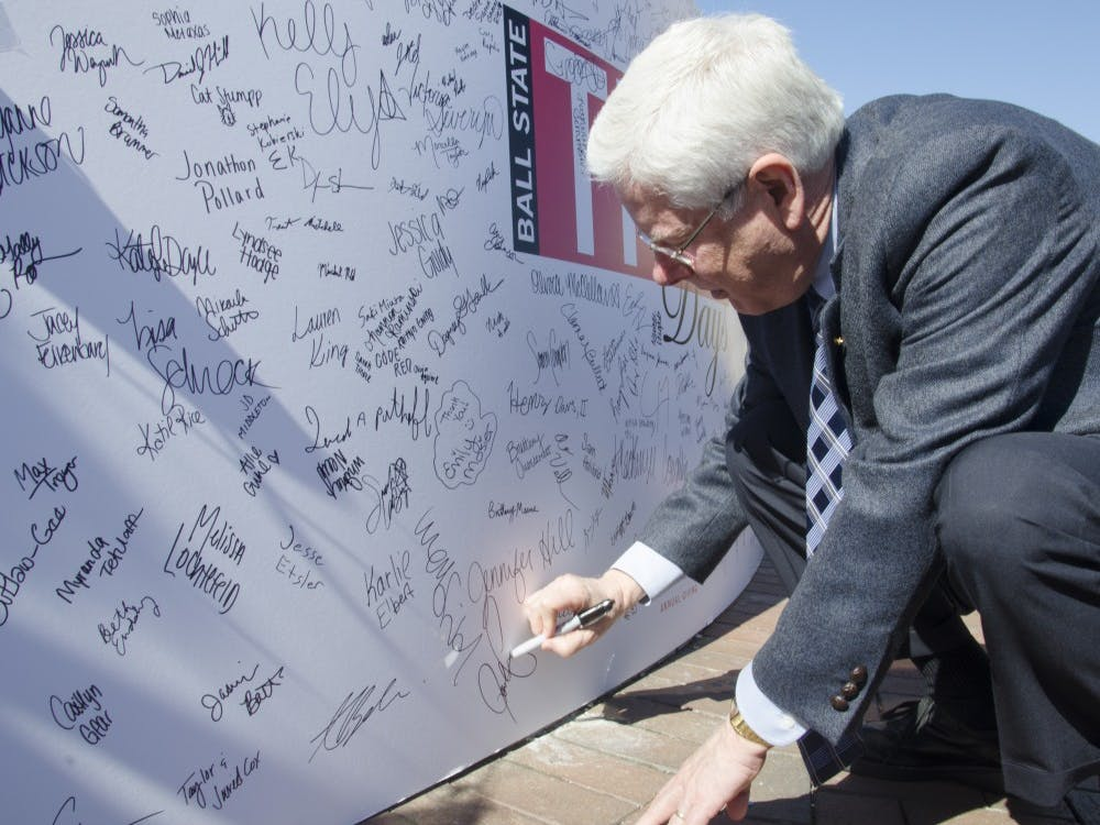 Ball State President Paul Ferguson signs the poster at the THAD Days on Oct. 8 at the Scramble Light. DN PHOTO BREANNA DAUGHERTY