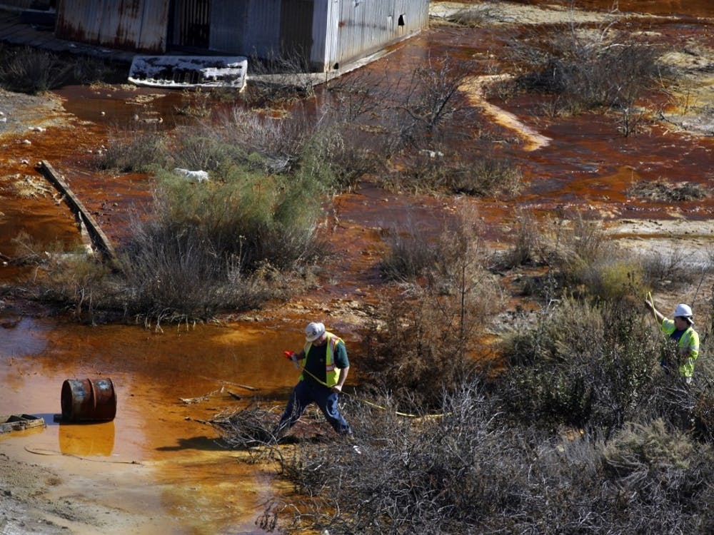 Hazardous waste crews, working with the EPA, measure the area of the upper pond that has turned orange from rust and contains mercury and sulfuric acid as seen at the deserted New Idria mercury mines, October 25, 2011. The mines, in rural San Benito County, were once a bustling community, but now the miners are gone, and the pollution remains. (Karen T. Borchers/San Jose Mercury News/MCT)