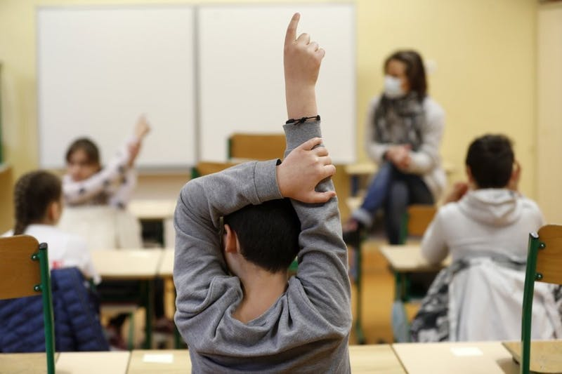 FILE - In this May 14, 2020 file photo, schoolchildren raise their fingers to answer their teacher Sandrine Albiez, wearing a face masks, in a school in Strasbourg, eastern France. France's government is admitting that not all classrooms can safely reopen Tuesday, Sept. 1, 2020 as planned. A persistent rise in virus infections is jeopardizing the government's push to get France's 12.9 million schoolchildren back into class.  (AP Photo/Jean-Francois Badias, File)