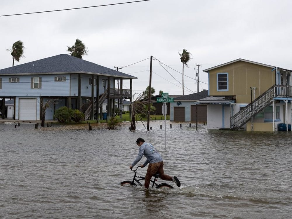 A boy rides his bike down South Magnolia Street in Rockport, Texas, as Tropical Storm Beta approaches on Monday, Sept. 21, 2020. (Courtney Sacco/Corpus Christi Caller-Times via AP)