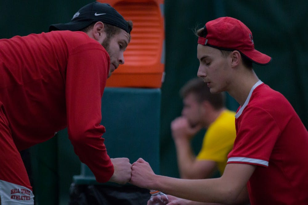 <p>Graduate Assistant Lucas Andersen talks with Chris Adams between tennis matches against the University of Toledo. Ball State won 5 to 2 on March 24 at Northwest YMCA in Muncie. <strong>Eric Pritchett, DN</strong></p>