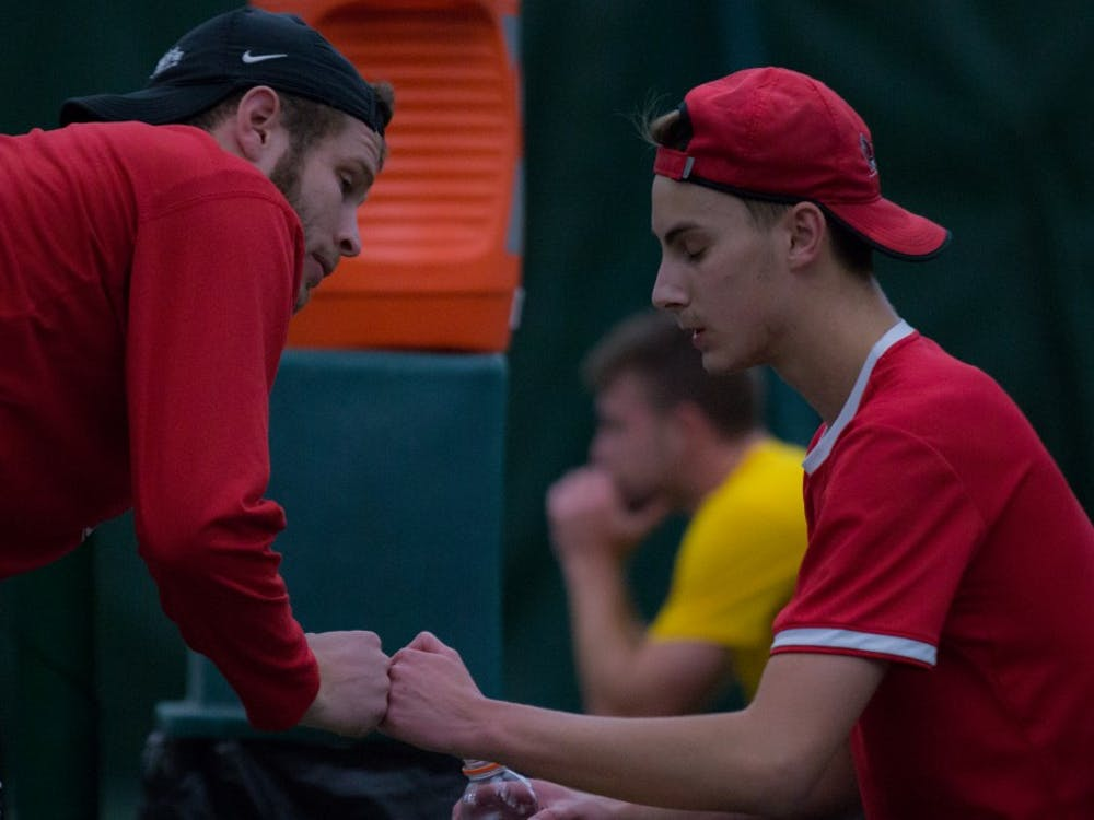 Graduate Assistant Lucas Andersen talks with Chris Adams between tennis matches against the University of Toledo. Ball State won 5 to 2 on March 24 at Northwest YMCA in Muncie. Eric Pritchett, DN