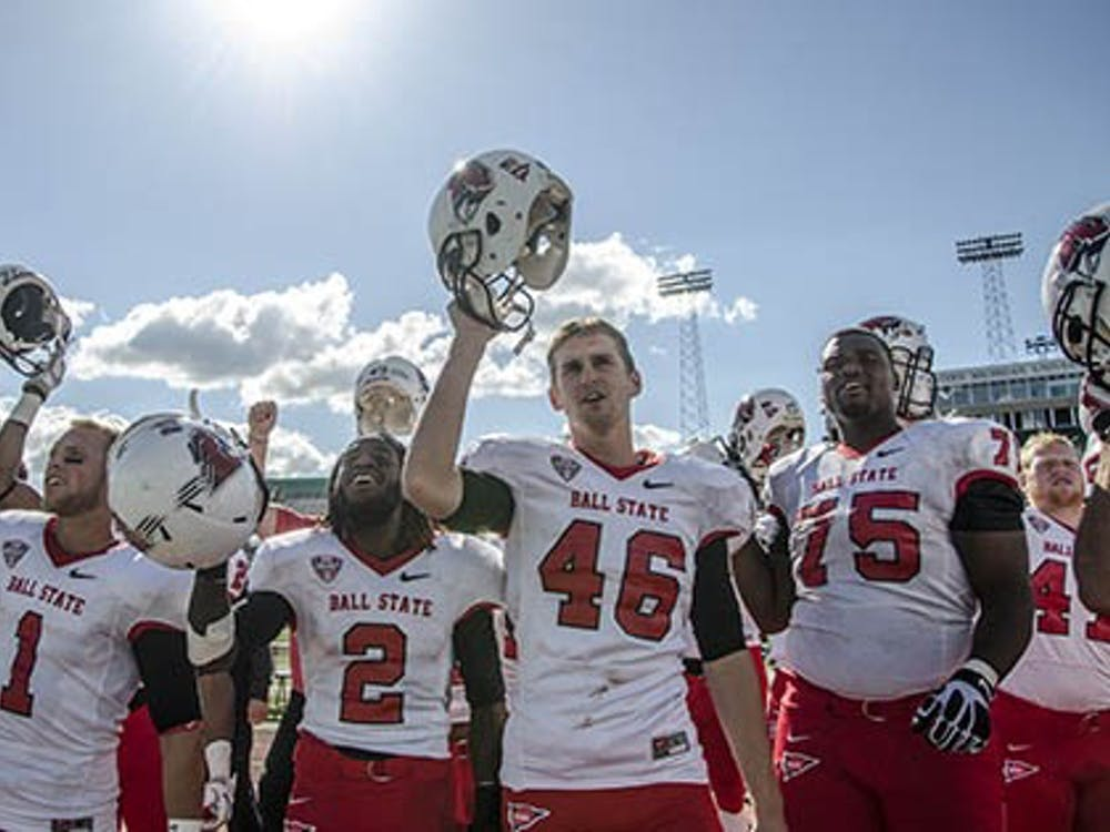 Ball State football players celebrate a victory against Eastern Michigan University by singing Ball State's Alma Mater. Ball State's win gave it a 3-1 record. DN PHOTO COREY OHLENKAMP
