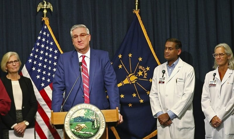 Indiana Gov. Eric Holcomb announces during a press conference at the Indiana Statehouse, Friday, March 6, 2020, in Indianapolis, that the first case of COVID-19 has been diagnosed in the state. Kristina Box, left, Indiana State Health Commissioner, and doctors from Community Health Network stand behind him. (Kelly Wilkinson/The Indianapolis Star via AP)