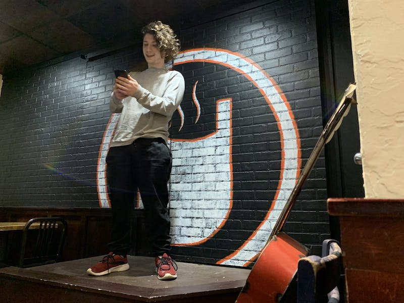 Tim Stewart reads the first poem he has ever written off of his phone Jan. 26, 2020, on stage at Cuplets at The Cup. Stewart said his goal for the new year is to try something new every month, so he made poetry his January activity. Taylor Smith, DN