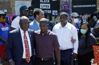 Family attorney Ben Crump, left, escorts Quincy Mason, second from left, a son of George Floyd, Wednesday, June 3, 2020, in Minneapolis, as they and some Floyd family members visited a memorial where Floyd was arrested on May 25 and died while in police custody. Video shared online by a bystander showed a white officer kneeling on his neck during his arrest as he pleaded that he couldn't breathe. (AP Photo/Jim Mone)