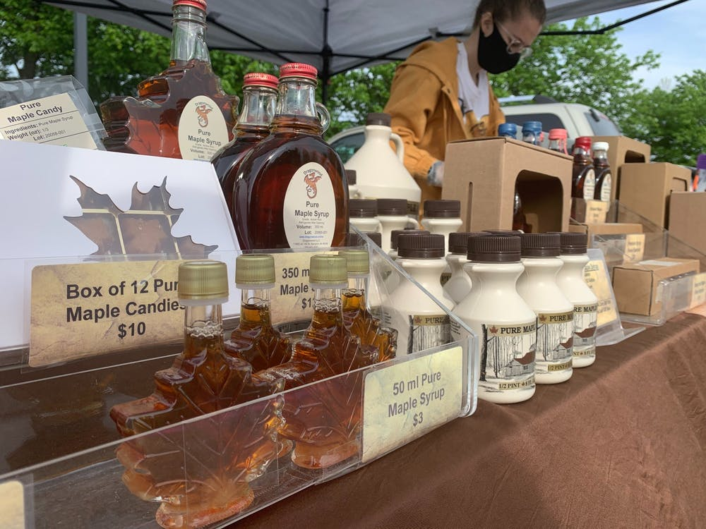 <p>Katie Ambs, intern for Dragoonwood LLC, sets up maple syrup and honey products at the start of the farmers market, May 23, 2020, at Minnetrista. Ambs said Dragonwood&nbsp;has been busy at other farmers markets as well around Indiana. <strong>Jenna Gorsage, DN</strong></p>