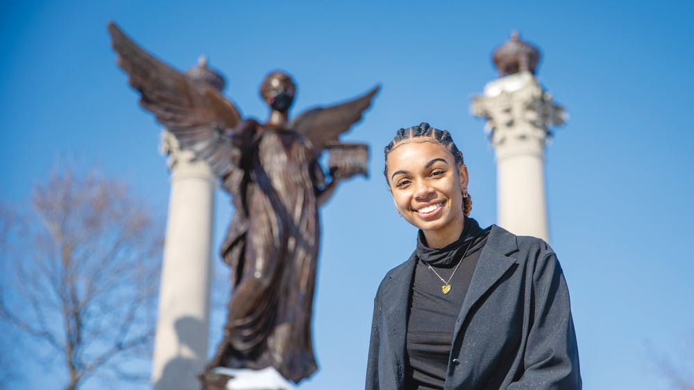 Senior public communications major Taylor Hall poses for a portrait in front of the Beneficence statue Feb. 19, 2021, in the Quad. Hall is the founder of Artivist LLC, a community outreach program. Kristen Triplett, DN