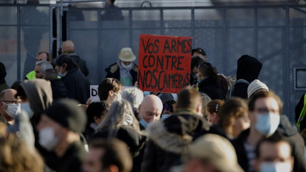Demonstrators gather during a protest against a bill on police images, in Paris, Saturday, Nov. 21, 2020. Thousands of people took to the streets in Paris and other French cities Saturday to protest a proposed security law they say would impinge on freedom of information and media rights. The board reads: Your guns against our cameras. (AP Photo/Christophe Ena)