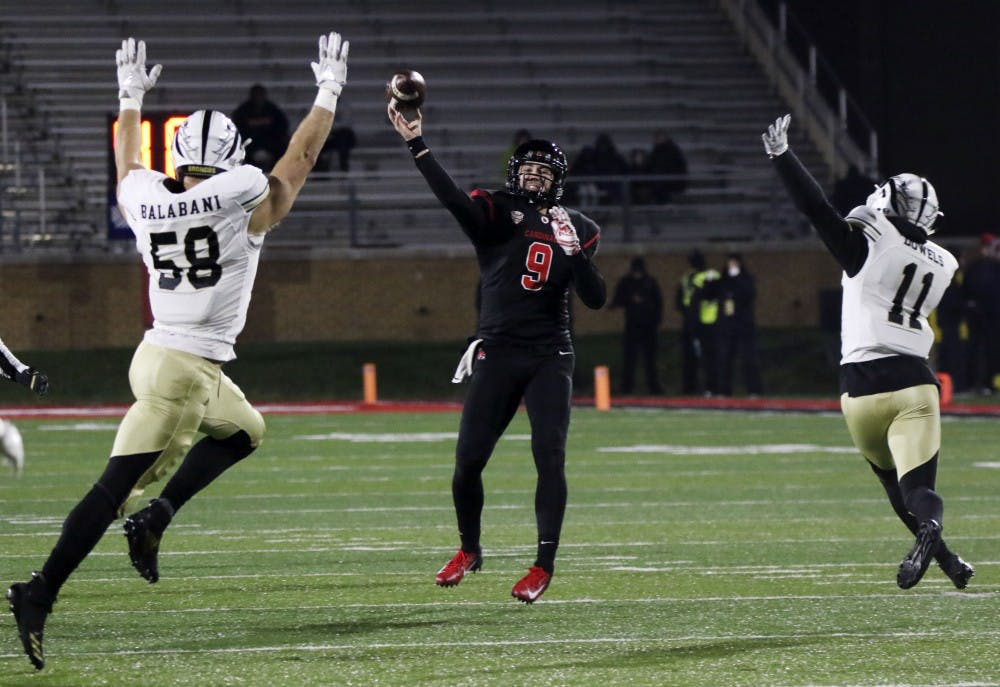 Ball State redshirt sophomore quarterback Drew Plitt passes the ball to a teammate while Western Michigan defenders try to knock the ball out of the air during the Cardinals' game against the Broncos Nov. 13, 2018, at Scheumann Stadium. Ball State won 42-41 in overtime on senior night. Paige Grider, DN