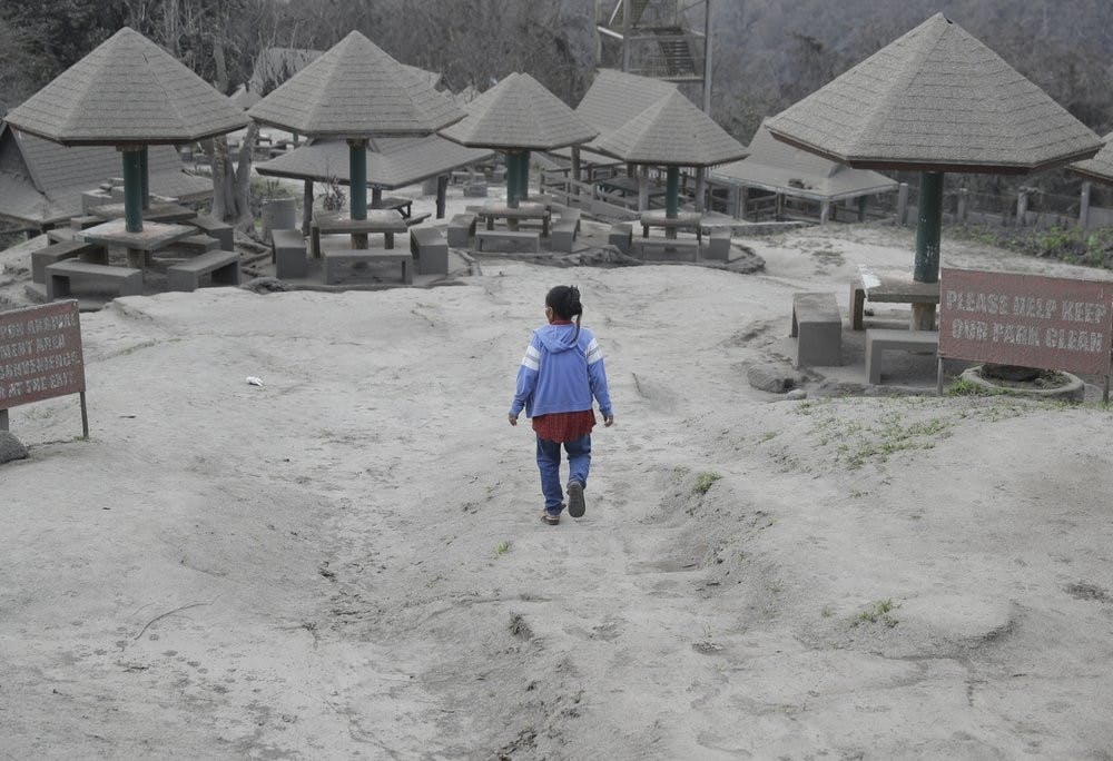 """<p>A woman walks along a park covered in volcanic-ash at a town Jan. 19, 2020, near Taal volcano in Tagaytay, Cavite province, in southern Philippines. Philippine officials said the government will no longer allow villagers to return to a crater-studded island where an erupting Taal volcano lies, warning that living there would be """"like having a gun pointed at you."""" <strong>(AP Photo/Aaron Favila)</strong></p>"""