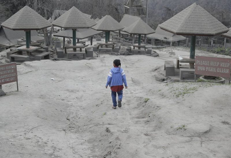 "A woman walks along a park covered in volcanic-ash at a town Jan. 19, 2020, near Taal volcano in Tagaytay, Cavite province, in southern Philippines. Philippine officials said the government will no longer allow villagers to return to a crater-studded island where an erupting Taal volcano lies, warning that living there would be ""like having a gun pointed at you."" (AP Photo/Aaron Favila)"