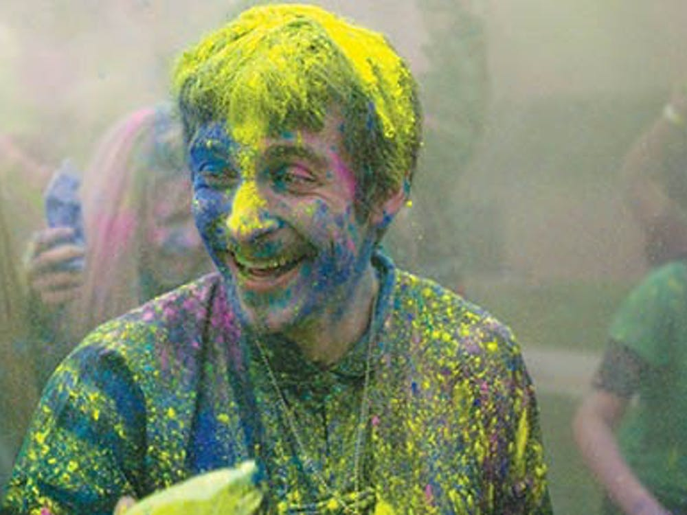 Senior sculpture major Nathan Ferrise laughs as he receives a blast of yellow chalk to his face during the Holi festival on April 19, 2013 at Noyer Complex. Holi is a Hindu celebration that honors the oncoming of spring, a time known to the Hindu people as a period of renewal. DN PHOTO RJ RICKER