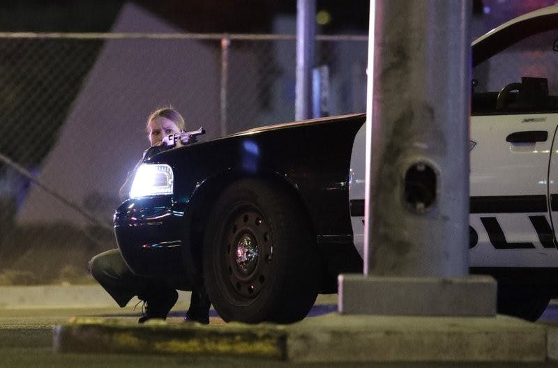 A police officer takes cover behind a police vehicle during a shooting near the Mandalay Bay resort and casino on the Las Vegas Strip Oct.1. Associated Press