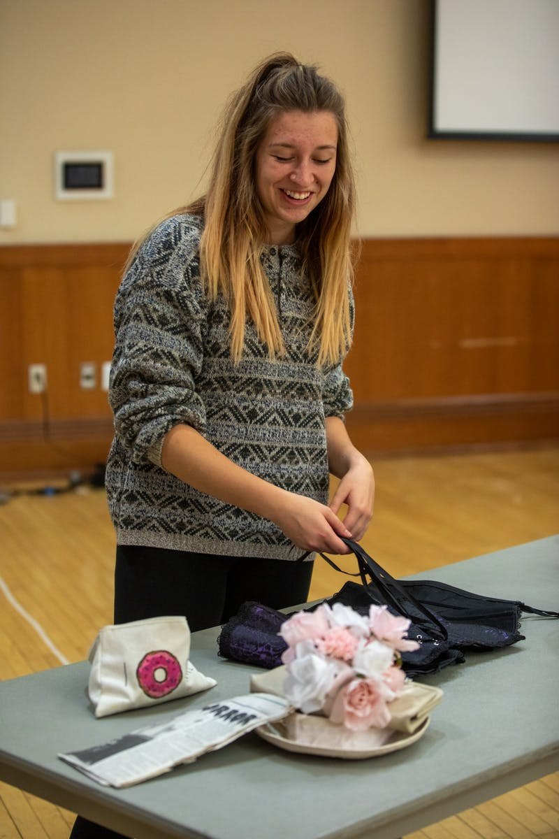 Costume Designer Dee Slagle gets a corset ready for a cast member Oct. 28, 2019, in the Student Center Ballroom. The practice was the last full run of the show the cast had before their show on Halloween. Jacob Musselman, DN