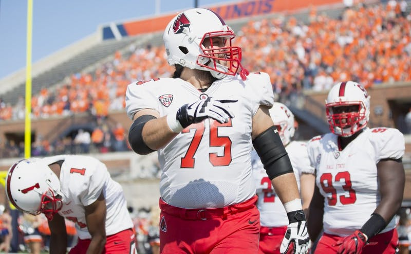 Ball State offensive lineman Vinnie Palazeti leads the team's captains onto the field before their match against the University of Illinois on Sept. 2. Robby General, DN File