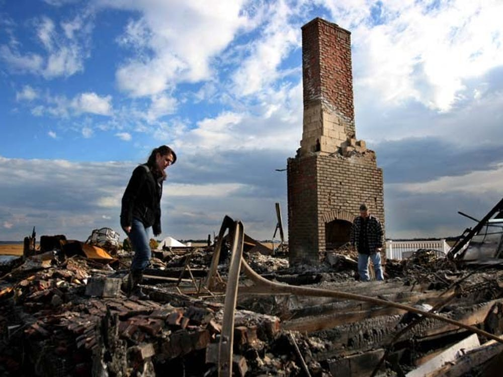Sal Quartucio, right, shown with niece Rachel Krinner, looks for belongings among the ashes of what use to be his home on Friday in Bayville, N.J. Sal and Elaine Quartucio's home burned down the night Hurricane Sandy hit the surrounding area. MCT PHOTO