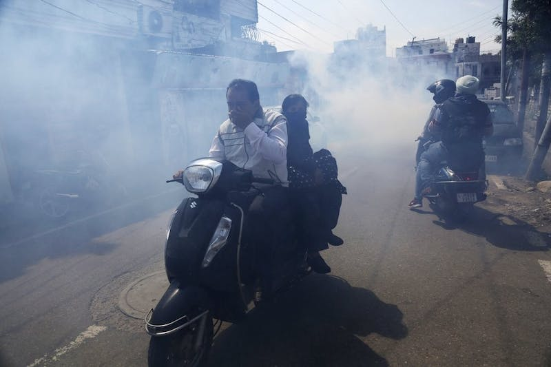 Indians ride two wheelers through smoke as municipal workers fumigate an area as a precautionary measure against the spread of new coronavirus March 16, 2020, in Jammu, India. For most people, the new coronavirus causes only mild or moderate symptoms. For some, it can cause more severe illness, especially in older adults and people with existing health problems. (AP Photo/Channi Anand)