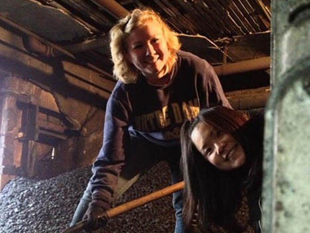 Elyse Brenner and Mayu Watanabe shovel $6,000 worth of coal into a furnace. This is the 10th year of Ball State's Alternate Spring Break program. DN PHOTO CARIEMA WOOD