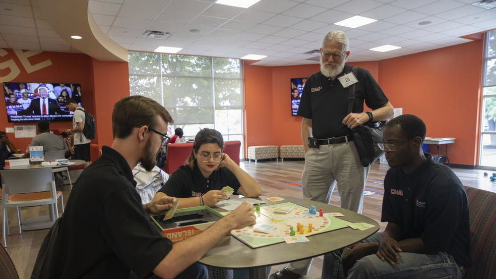 Students Joe Schmidt, Gwyn Hultquist, and Brian Walker play a board game while professor Dave Largent watches September 16th, 2019. Largent created the immersive learning class CS4MS+ to teach computer science to K-12 minority students. Robbie Mehling, Photo Provided