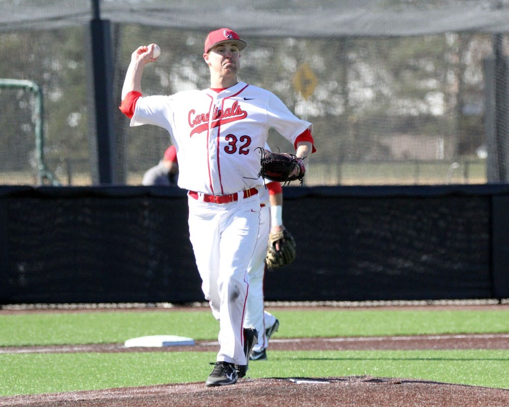 Pitcher David Current attempts to throw out a runner at first during the Cardinals' game against Purdue on March 22 at Ball Diamond. Ball State allowed five runs in the fourth inning. Paige Grider // DN