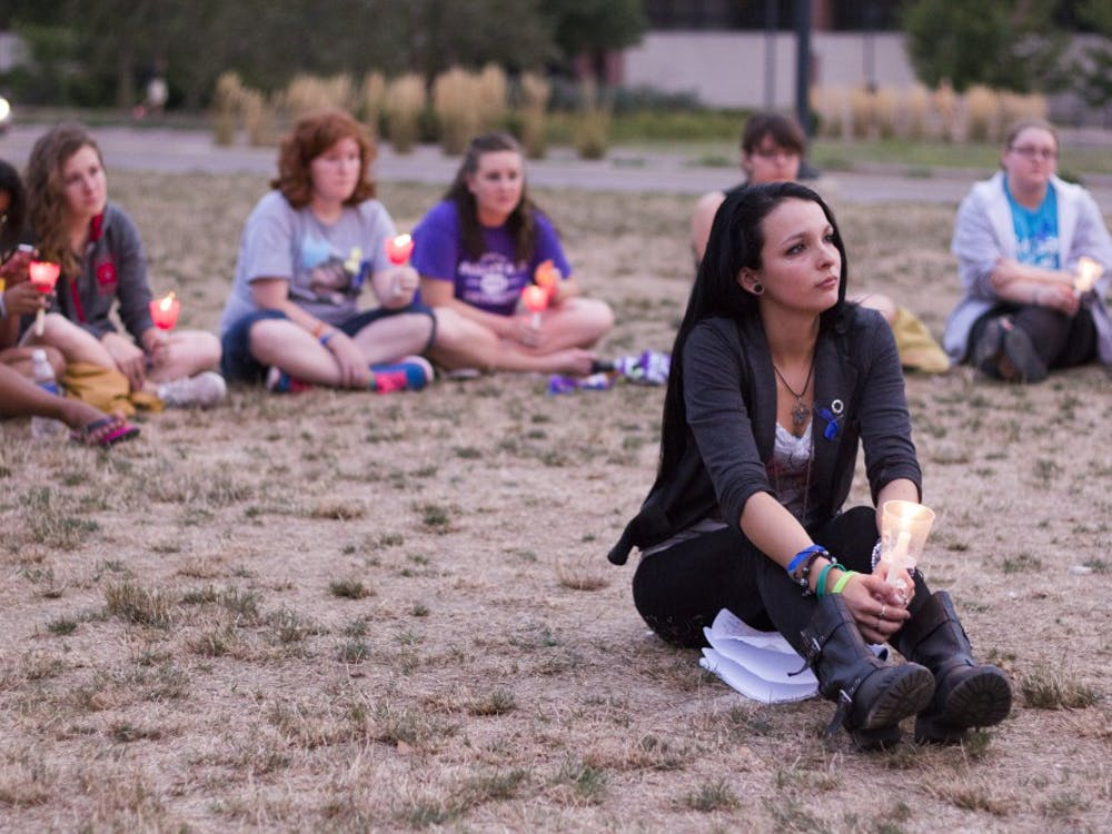 Carmen Diaz, a senior social work major, listens to a victims story at the Suicide Awareness Candlelight Vigil on Sept. 10. The vigil honored victims and survivors of suicide and those with depression. DN FILE PHOTO EMMA ROGERS