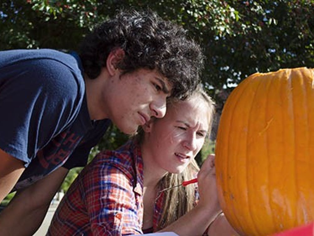 Sophomore actuarial science major Ben Fehler and his teammate junior telecommunications major Jes Wade begin the details on their pumpkin during the pumpkin carving contest at Fall Fest on Oct. 4. Fehler and Wade won first place with their carving of Charmander from Pokemon. DN PHOTO BREANNA DAUGHERTY