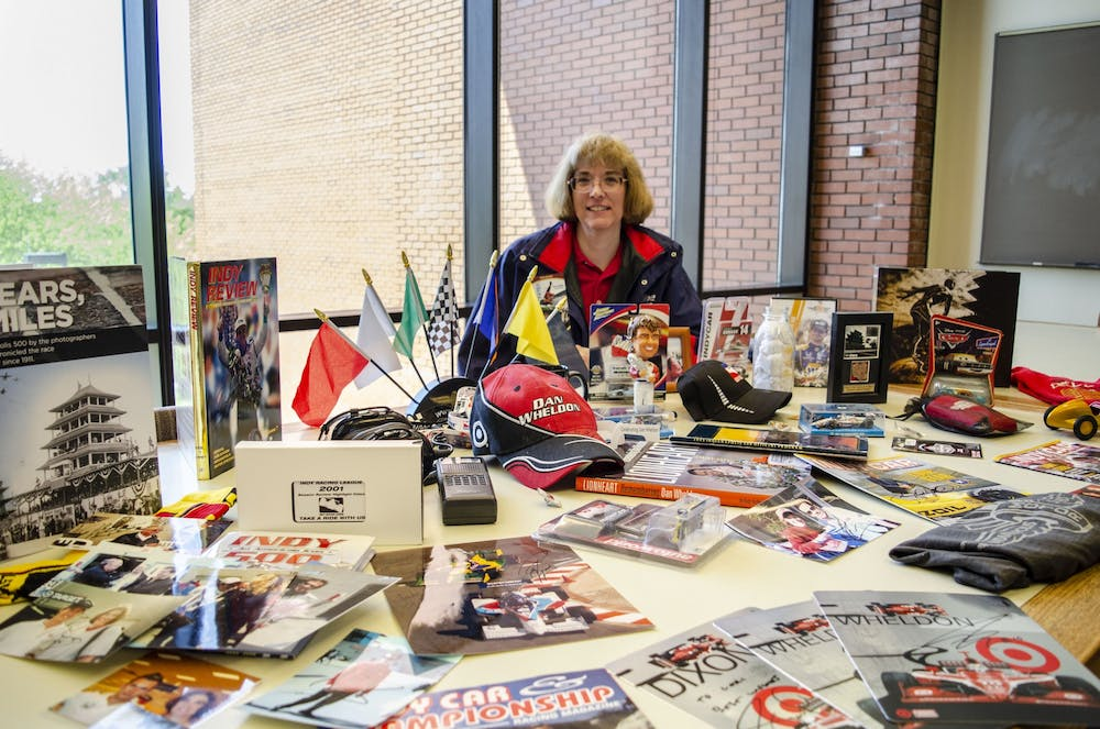 <p>Lori Siefker sits behind a portion of her IndyCar memorabilia collection May 14, 2019, in Bracken Library. The collection pictured is a small fraction of everything she has amassed over the years. <strong>Stephanie Amador, DN</strong></p>