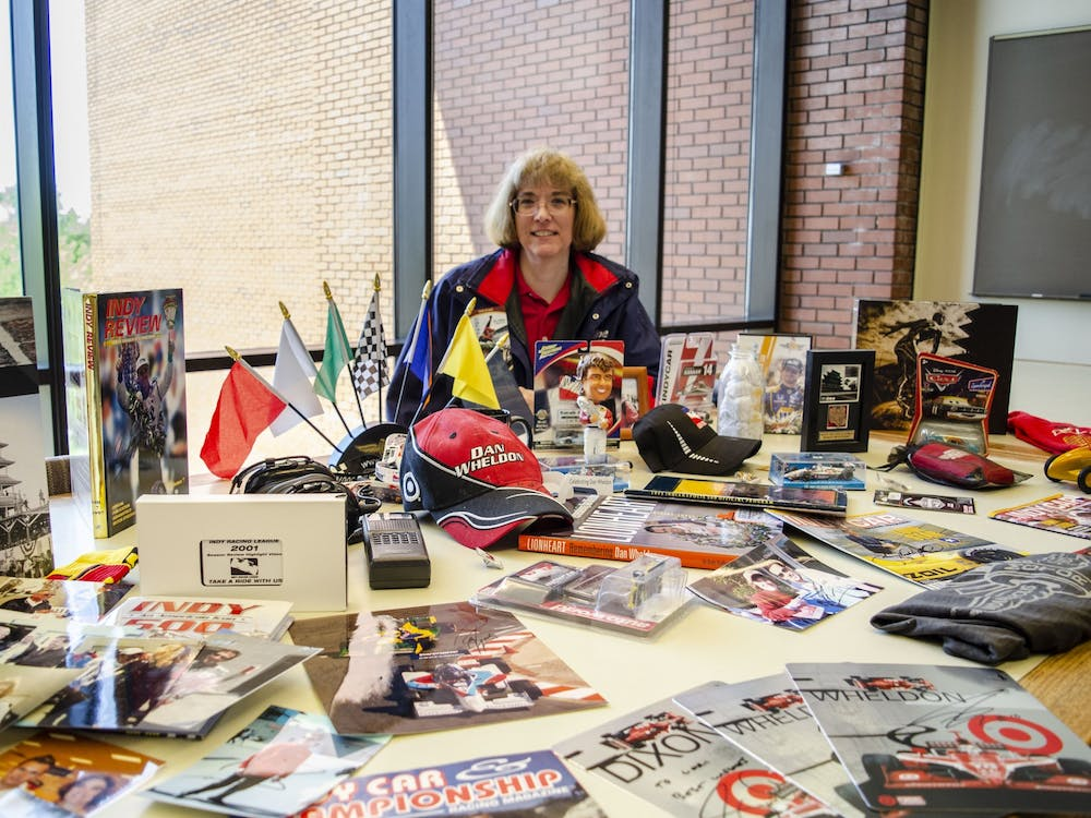 Lori Siefker sits behind a portion of her IndyCar memorabilia collection May 14, 2019, in Bracken Library. The collection pictured is a small fraction of everything she has amassed over the years. Stephanie Amador, DN