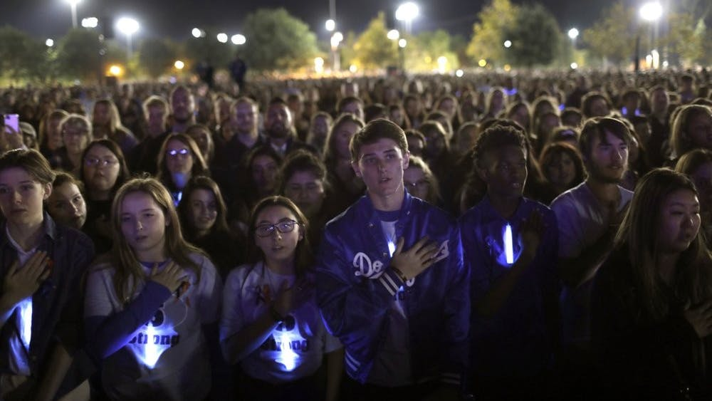 Students say the Pledge of Allegiance as thousands gather at a candlelight vigil for several students killed in the Saugus High School shooting in Central Park, Sunday, Nov. 17, 2019, in Santa Clarita, Calif. Detectives were searching for a motive for the killings carried out by the shooter on his 16th birthday. (Carolyn Cole/Los Angeles Times via AP)