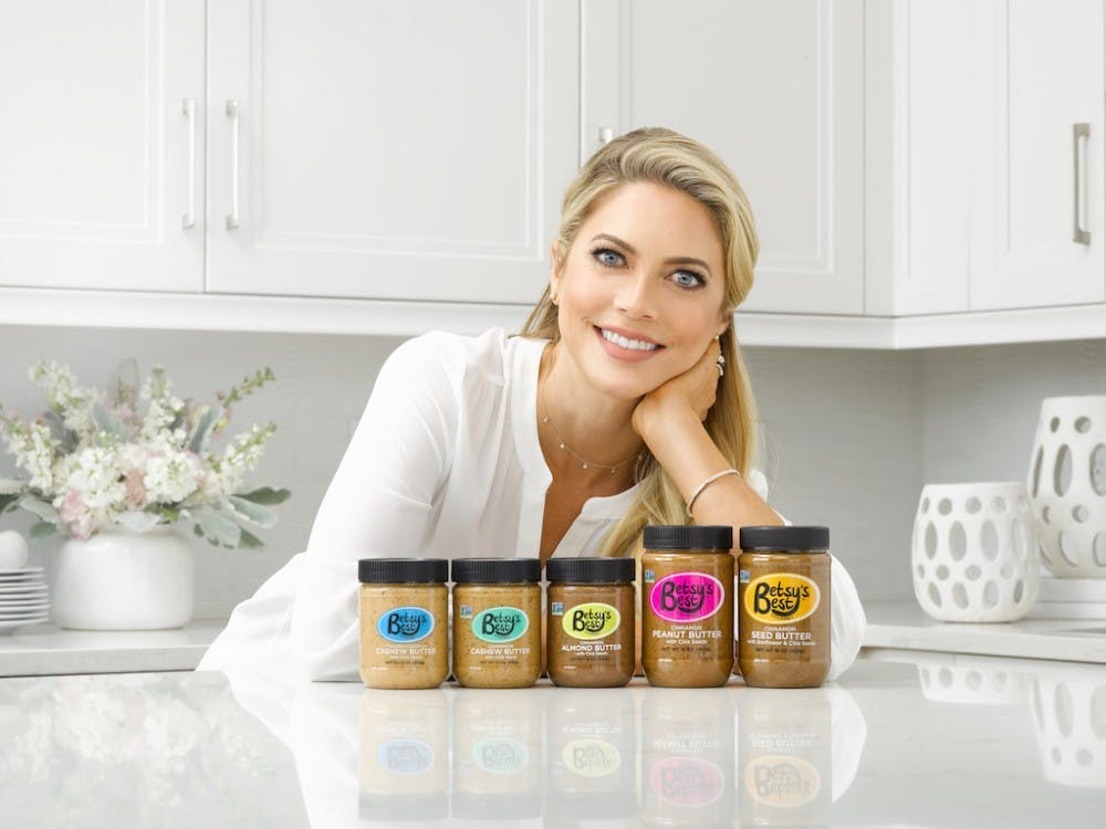 Alumna Betsy Opyt stands with the five nut butters she created in five years. Opyt opened Betsy's Best, her gourmet nut and seed butter company, after her daughter would not eat butters she brought home from the grocery store. Photo provided