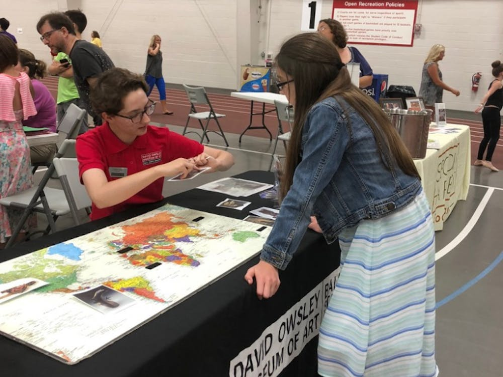 Senior Joan Seig explains the location and culture of a piece of art on Saturday, June 9, 2018 at Festival on the Green in Muncie, IN. Seig helped organized public outreach events throughout the summer as a program intern at the David Owsley Museum of Art. Photo provided.