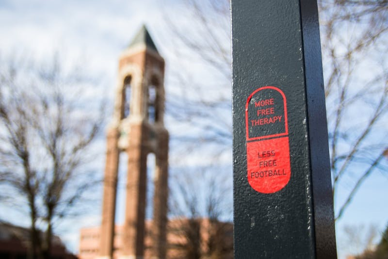 "Pill stickers are scattered around campus that say ""More Free Therapy, Less Free Football."" Reagan Allen // DN"
