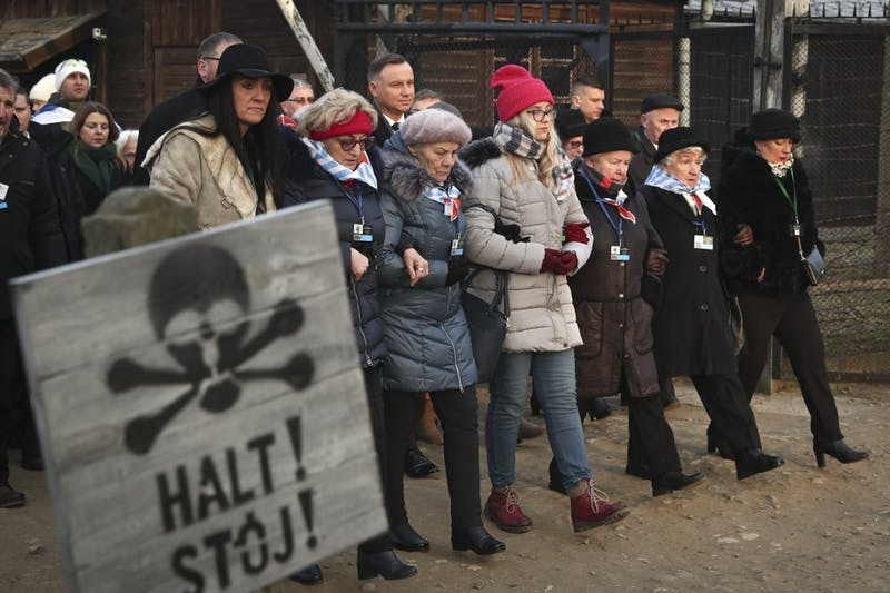 Poland's President Andrzej Duda walks along with survivors through the gates of the Auschwitz Nazi concentration camp Jan. 27, 2020, in Oswiecim, Poland. Survivors of the Auschwitz-Birkenau death camp gathered for commemorations marking the 75th anniversary of the Soviet army's liberation of the camp, using the testimony of survivors to warn about the signs of rising anti-Semitism and hatred in the world today. (AP Photo/Czarek Sokolowski)