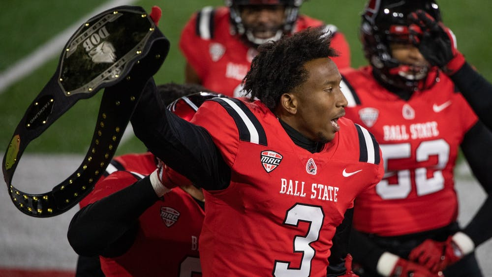 Ball State junior cornerback Amechi Uzodinma II holds up the defence celebration wrestling belt Nov. 18, 2020, at Scheumann Stadium. Uzodinma had one interception against the Huskies. Jacob Musselman, DN