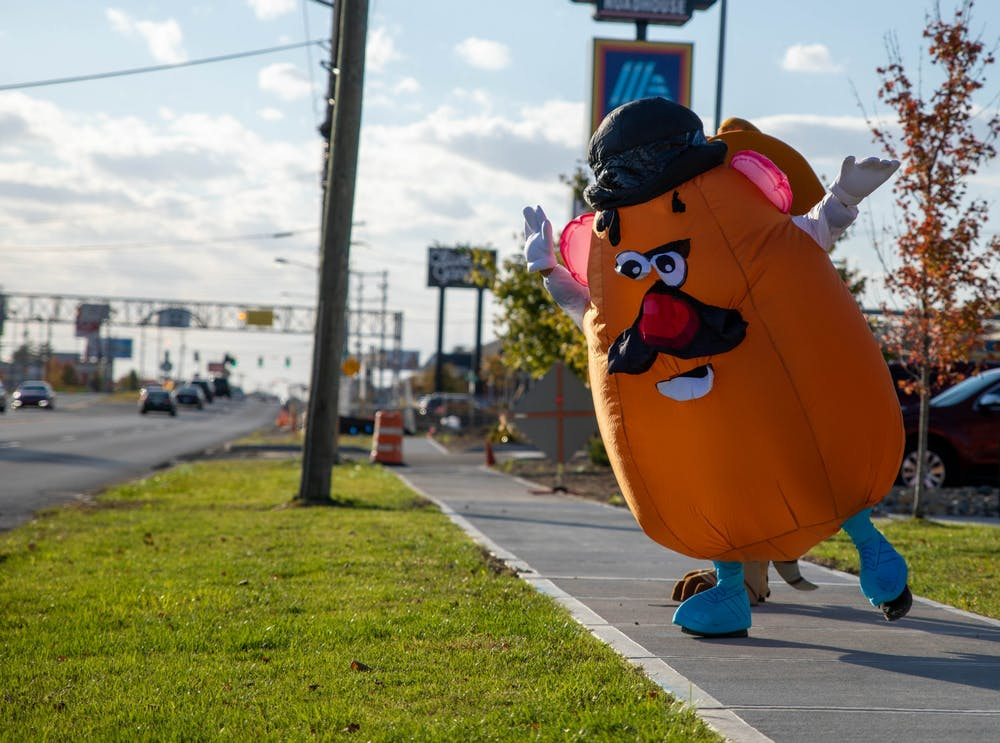 <p>Matthew Peiffer, dressed in a Mr. Potato Head costume, dances on the sidewalk Oct. 16, 2020, outside Texas Roadhouse in Muncie. Peiffer started dressing up in various costumes to bring happiness to children. <strong>Jaden Whiteman, DN</strong></p>