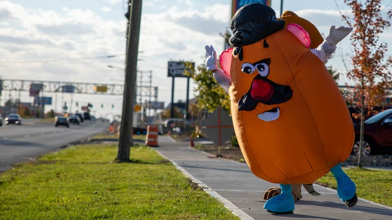 Matthew Peiffer, dressed in a Mr. Potato Head costume, dances on the sidewalk Oct. 16, 2020, outside Texas Roadhouse in Muncie. Peiffer started dressing up in various costumes to bring happiness to children. Jaden Whiteman, DN